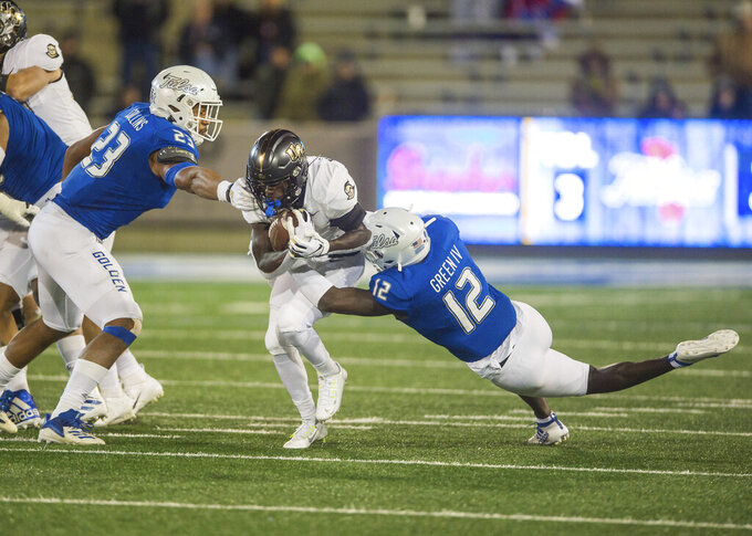 Tulsa  cornerback Allie Green IV (12) and linebacker Zaven Collins tackle Central Florida running back Adrian Killins Jr. during the second half of an NCAA college football game, Friday, Nov. 8, 2019 in Tulsa, Okla. (Brett Rojo/Tulsa World via AP)