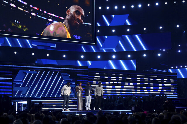Nathan Morris, from left, Wanya Morris, Shawn Stockman, of Boyz II Men, and Alicia Keys, second left, sing a tribute in honor of the late Kobe Bryant, seen on screen, at the 62nd annual Grammy Awards on Sunday, Jan. 26, 2020, in Los Angeles. (Photo by Matt Sayles/Invision/AP)