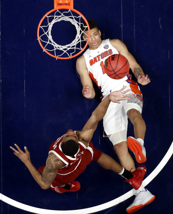 Florida forward Keyontae Johnson falls on the court as Arkansas forward Reggie Chaney, bottom, shoots in the second half of an NCAA college basketball game at the Southeastern Conference tournament Thursday, March 14, 2019, in Nashville, Tenn. Florida won 66-50. (AP Photo/Mark Humphrey)