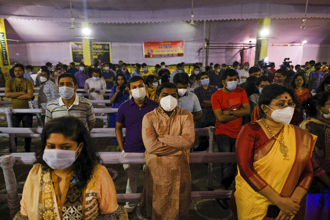FILE- In this Oct. 22, 2020 file photo, people wearing masks as a precautionary measure against the coronavirus assemble to offer prayers at Dhakeshwari Temple during Durga Puja festival in Dhaka, Bangladesh. Bangladesh is enforcing a lockdown for a week from Monday, shutting shopping malls and transportation, to help curb the spread of coronavirus as the rate of infections and deaths have increased in recent weeks.  (AP Photo/Mahmud Hossain Opu,File )