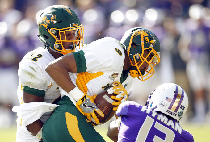 FILE - In this Jan. 6, 2017, file photo, North Dakota State cornerback Marquise Bridges (9) intercepts a pass intended for James Madison wide receiver Ishmael Hyman (13) as North Dakota State linebacker Jabril Cox (42) closes in on the play during the third quarter in the FCS championship NCAA college football game at Toyota Stadium in Frisco, Texas. Cox is one of the few returning starters for the Bison, who are replacing eight players on offense and seven on defense from a team that won the school's seventh national championship in seven years. Despite all the holes to fill, North Dakota State is ranked No. 1 in a preseason poll of FCS coaches. (Vernon Bryant/The Dallas Morning News via AP, File)
