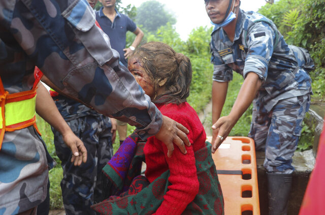 An injured girl is rescued after a landslide stuck early Sunday in Sindhupalchowk district, about 120 kilometers (75 miles) east of the capital, Kathmandu, Nepal, Monday, Sept.14, 2020. Rescuers resumed searching on Monday for people missing since a deadly landslide struck three villages in Nepal's mountains, authorities said. (AP Photo/Niroj Chaulagai)