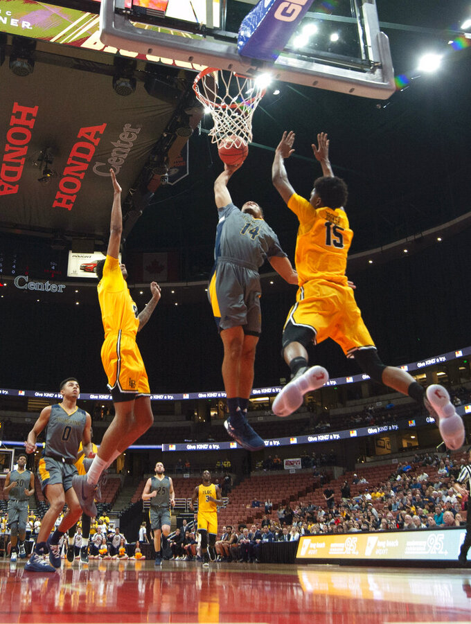 UC Irvine guard Evan Leonard, center, goes up for a dunk next to Long Beach State guard Deishuan Booker, right, during the first half of an NCAA college basketball game at the Big West men's tournament in Anaheim, Calif., Friday, March 15, 2019. (AP Photo/Kyusung Gong)