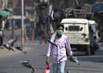 Pigeons fly as a man wearing a mask walks past in Srinagar, Indian controlled Kashmir, Monday, July 13, 2020. Authorities reimposed lockdown on Monday in parts of Indian-controlled Kashmir, including the region's main city, following surge in coronavirus cases. (AP Photo/Mukhtar Khan)