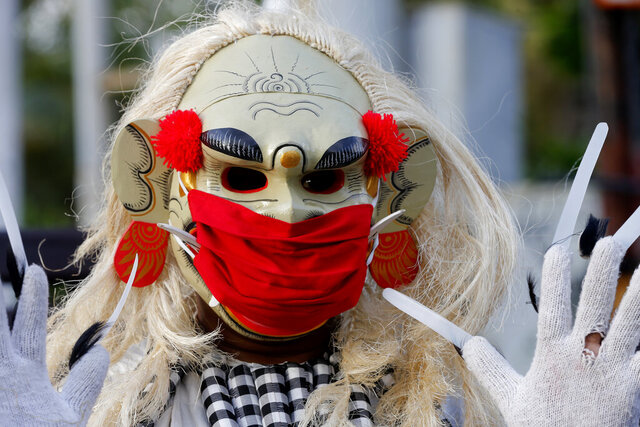 A man wearing a traditional Balinese celuluk costume with a face mask as a precaution against the coronavirus during a campaign to keep on wearing masks in public places in Bali, Indonesia, Saturday, Oct. 3, 2020. (AP Photo/Firdia Lisnawati)