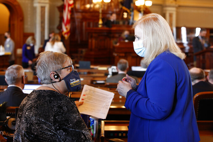 Kansas state Reps. Brenda Landwehr, left, R-Wichita, and Susan Concannon, R-Beloit, confer during a House debate on a proposed anti-abortion amendment to the Kansas Constitution, Friday, Jan. 22, 2021, at the Statehouse in Topeka, Kan. Both supported the measure, which would overturn a Kansas Supreme Court decision in 2019 that declared access to abortion a