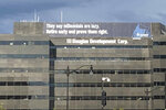 In this June 13, 2019 photo, a retirement advertisement sign is shown on a building in Washington.  Nearly one-quarter of Americans say they never plan to retire, according to a poll that suggests a disconnection between individuals' retirement plans and the realities of aging in the workforce.  (AP Photo/Nancy Benac)