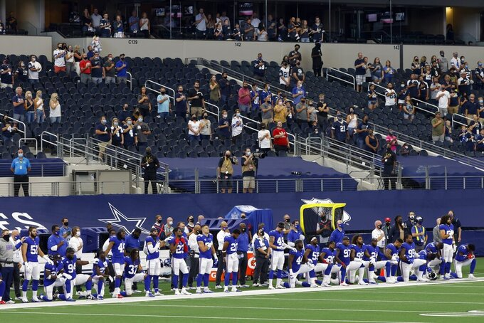 Players and staff of the New York Giants stand and kneel as they and fans in attendance listen to the national anthem before the first half of an NFL football game against the Dallas Cowboys in Arlington, Texas, Sunday, Oct. 11, 2020. (AP Photo/Ron Jenkins)