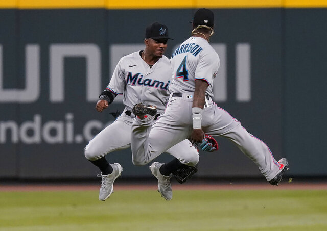 Miami Marlins outfielders Monte Harrison, right, and Starling Marte celebrate the team's 8-0 win over the Atlanta Braves in a baseball game Tuesday, Sept. 8, 2020, in Atlanta. (AP Photo/Brynn Anderson)