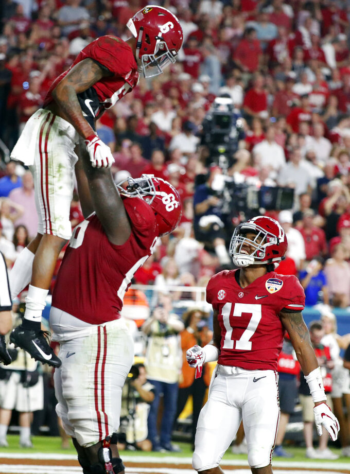 Alabama offensive lineman Lester Cotton Sr. (66) lifts Alabama wide receiver DeVonta Smith (6) after Smith scored a touchdown, during the second half of the Orange Bowl NCAA college football game against Oklahoma, Saturday, Dec. 29, 2018, in Miami Gardens, Fla.To the right is Alabama wide receiver Jaylen Waddle (17). (AP Photo/Wilfredo Lee)
