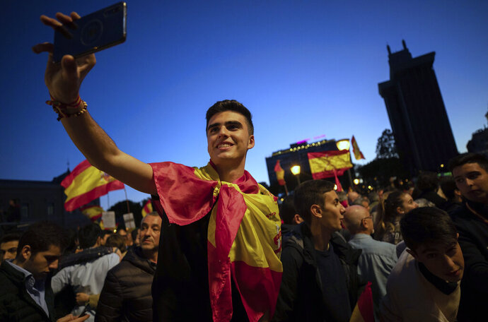 FILE - In this Friday, April 26, 2019 file photo, far-right Vox party supporters attend an election campaign event in Madrid, Spain. In Spain, Vox's gains have come at the expense of traditional conservatives, who were slow to counter the upstart party's rise among the young. Its events include the popular
