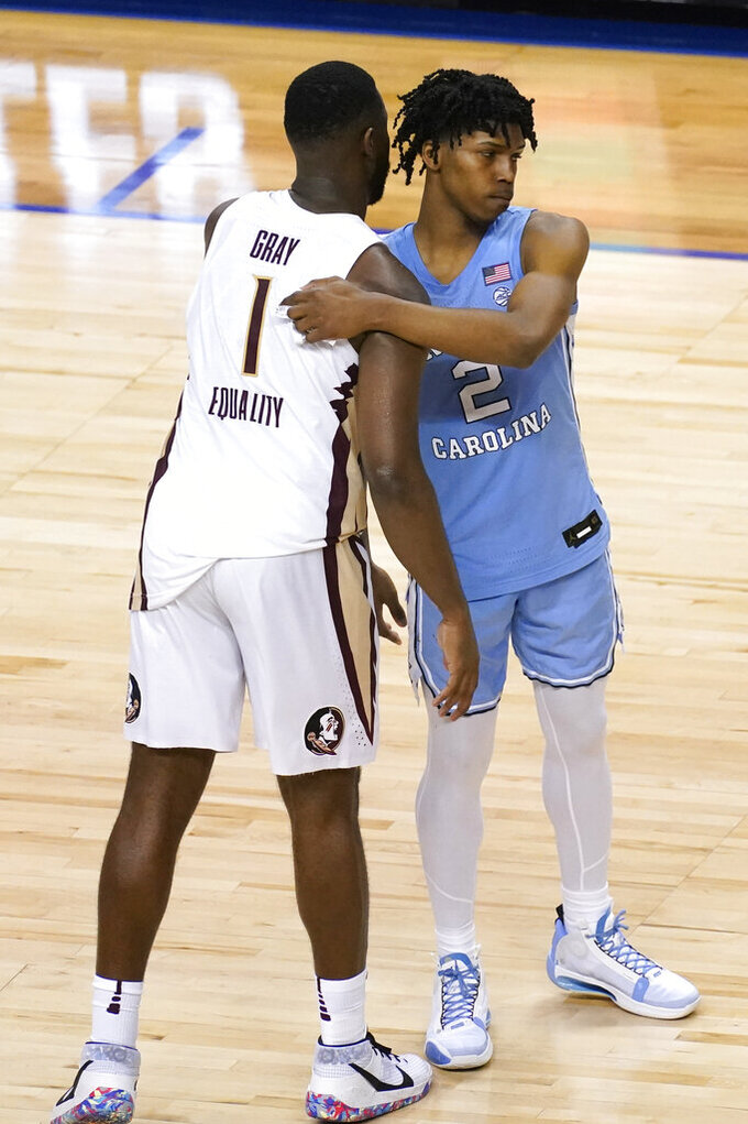 Florida State forward RaiQuan Gray (1) consoles North Carolina guard Caleb Love (2) after an NCAA college basketball game in the semifinal round of the Atlantic Coast Conference tournament in Greensboro, N.C., Friday, March 12, 2021. Florida State won the game 69-66. (AP Photo/Gerry Broome)