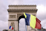 Yellow vest protesters brandish national flags as they gather around the Arc de Triomphe to keep pressure on French President Emmanuel Macron's government, for the 13th straight weekend of demonstrations, in Paris, France, Saturday, Feb. 9, 2019. (AP Photo/Kamil Zihnioglu)