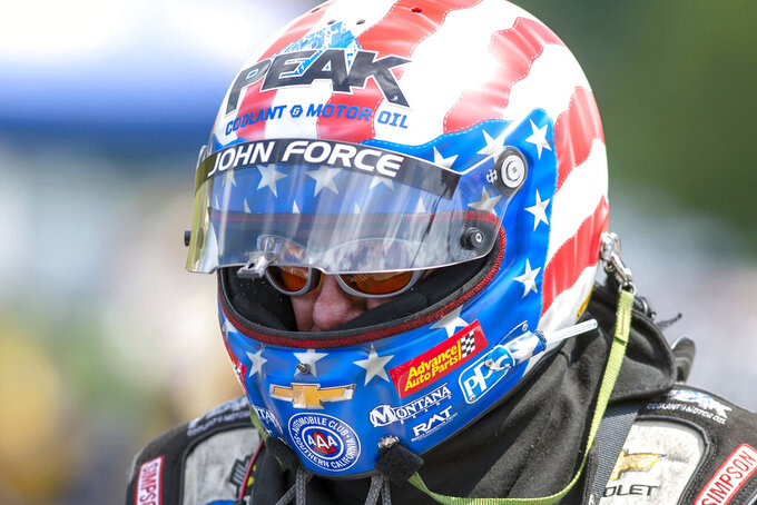 FILE - In this June 16, 2019, file photo, Funny Car driver John Force prepares to run in the finals at the NHRA Thunder Valley Nationals at Bristol Dragway in Bristol, Tenn. More than a half century after he began piloting dragsters, Force, 70, will be in his Funny Car this weekend for the start of a new season in Pomona, Calif. (David Crigger/Bristol Herald Courier via AP, File)