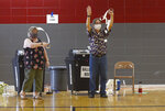 Exit clerks Mary Ella Young and Patrick Voll let a voter know where they and the ballot boxes are, at a polling place in a high school gym Tuesday, June 2, 2020, in Terre Haute, Ind. Joseph C. Garza/The Tribune-Star via AP)