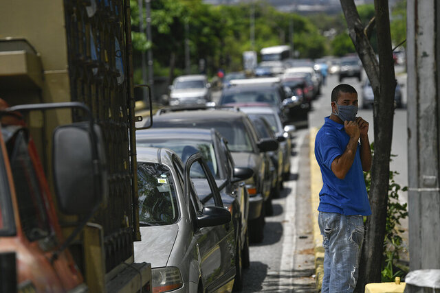 Vehicles wait in line to fill up with fuel at a gas station in Caracas, Venezuela, Tuesday, June 2, 2020. Starting June, Venezuelans pay international market fuel prices, with limited access to subsidized gasoline each month, marking a historic break in the country's practice of having the world's cheapest fuel. (AP Photo/Matias Delacroix)