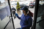Employee Gina Hansen, right, enters her office to retrieve documentation for a client outside Daniel J. Schaefer Funeral Home Thursday, April 2, 2020, in the Brooklyn borough of New York. The company is equipped to handle 40-60 cases at a time. But amid the coronavirus pandemic, it was taking care of 185 Thursday morning. (AP Photo/John Minchillo)