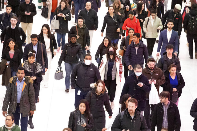 Three commuters, center, wear masks as they walk through the World Trade Center transportation hub, Wednesday, March 4, 2020, in New York. (AP Photo/Mark Lennihan)