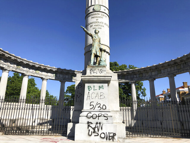 A monument to Confederate President Jefferson Davis in Richmond, Va., is covered with graffiti on Sunday, May 31, 2020, after overnight protests over the death of George Floyd. Many of the city's most prominent Confederate monuments were tagged with similar graffiti. Protests were held in U.S. cities over the death of Floyd, a black man who died after being restrained by Minneapolis police officers on May 25.  (AP Photo/ Sarah Rankin)