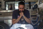 A man grieves besides bodies of a politician Sheikh Wasim Bari and his brother, inside an ambulance in Bandipora town, north of Srinagar, Indian controlled Kashmir, Thursday, July 9, 2020. Unidentified assailants late Wednesday fatally shot Bari, a leader with Prime Minister Narendra Modi's Bharatiya Janata Party, along with his father and brother in Kashmir, police said, in a first major attack against India's ruling party members in the disputed region. (AP Photo/ Dar Yasin)