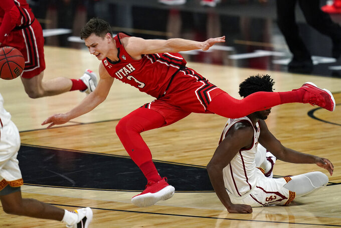Utah's Pelle Larsson (3) falls over Southern California's Chevez Goodwin (1) during the first half of an NCAA college basketball game in the quarterfinal round of the Pac-12 men's tournament Thursday, March 11, 2021, in Las Vegas. (AP Photo/John Locher)