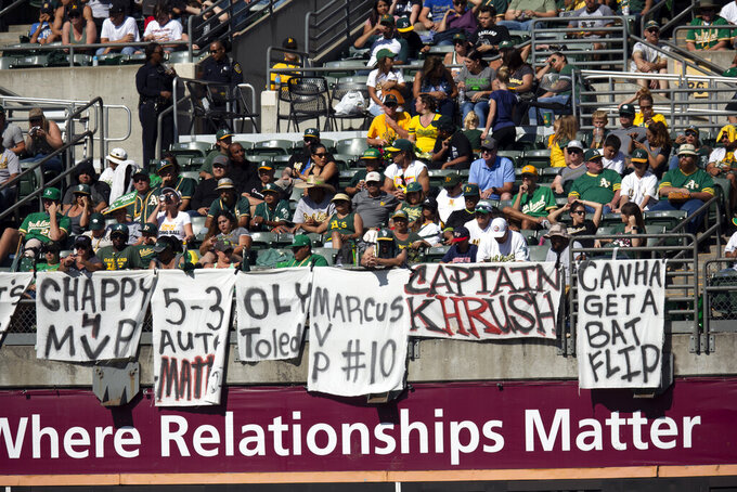 """FILE - In this Sept. 22, 2019, file photo, Oakland Athletics fans drape the bleachers with messages for the team during the A's baseball game against the Texas Rangers in Oakland, Calif. Baseball players and owners are currently caught in a bitter dispute over how to start amid the coronavirus pandemic. Both sides occasionally mention fans, talking about doing right by them. But apart from taking sides, how do the fans feel -- would they consider a severely shortened schedule as legit? """"I think any rate-based stat record -- batting average, ERA -- would have to be considered an anomaly,"""" Oakland fan Adam Brooks said. (AP Photo/D. Ross Cameron, File)"""