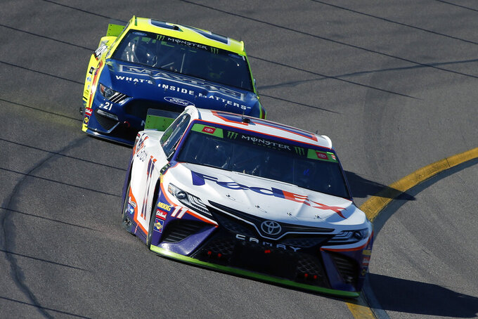 Denny Hamlin (11) drives through Turn 4 in front of Paul Menard during a NASCAR Cup Series auto race at ISM Raceway, Sunday, Nov. 10, 2019, in Avondale, Ariz. (AP Photo/Ralph Freso)
