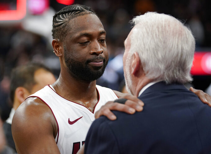 Miami Heat guard Dwyane Wade, left, embraces San Antonio Spurs coach Gregg Popovich after an NBA basketball game Wednesday, March 20, 2019, in San Antonio. Miami won 110-105. (AP Photo/Darren Abate)