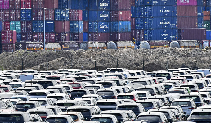 FILE - In this Wednesday, June 3, 2020 photo new cars are stored in front of containers at the 'logport' (logistic port) in Duisburg, Germany.  Official statistics show that the German economy grew 0.3% in last year's fourth quarter compared with the previous three-month period — a better performance than first thought. (AP Photo/Martin Meissner, file)