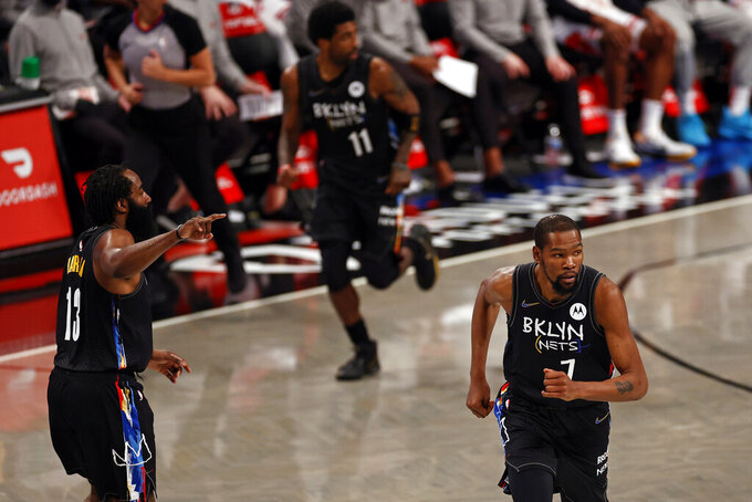 Brooklyn Nets guard James Harden (13), forward Kevin Durant (7) and guard Kyrie Irving (11) run up-court against the Chicago Bulls during the first half of an NBA basketball game Saturday, May 15, 2021, in New York. The Nets won 105-91. (AP Photo/Adam Hunger)