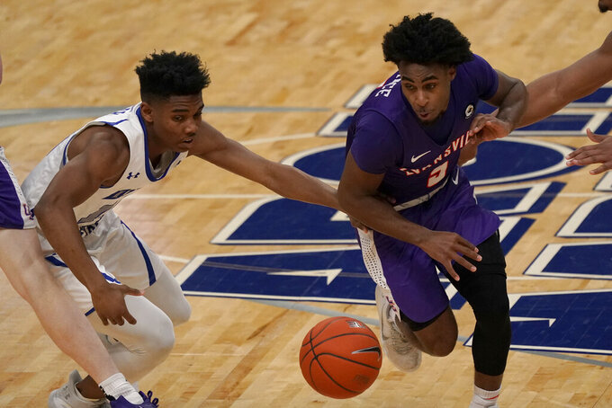 Evansville's Shamar Givance, right, heads to the basket past Indiana State's Julian Larry during the first half of an NCAA college basketball game in the quarterfinal round of the Missouri Valley Conference men's tournament Friday, March 5, 2021, in St. Louis. (AP Photo/Jeff Roberson)