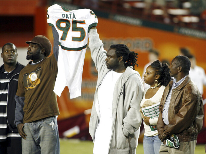 FILE - In this Nov. 23, 2006, file photo, Bryan Pata's family hold up his jersey at the beginning of an NCAA college football game between Miami and Boston College at the Orange Bowl in Miami. Rashaun Jones, 35, of Lake City, a former University of Miami football player was arrested Thursday, Aug. 19, 2021, in connection with the 2006 fatal shooting of his teammate Bryan Pata. Pata, a 22-year-old, 6-foot-4, 280-pound defensive lineman, was shot several times outside of his Kendall, Fla., apartment the night of Nov. 7, 2006. (AP Photo/Luis M. Alvarez, File)