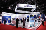 Visitors are seen at the booth of Airbus during the opening trade day of the Singapore Airshow 2020 in Singapore Tuesday, Feb. 11, 2020. Singapore's air show began Tuesday with the usual ribbon cutting, but less typical warnings to industry and military figures attending to avoid handshakes and other close contact to avoid spreading a virus that has sickened tens of thousands of people. (AP Photo/Danial Hakim)