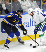 St. Louis Blues' Ryan O'Reilly (90) reaches for the puck with Vancouver Canucks' Jordie Bern (4) during the first period of an NHL hockey game, Thursday, Oct. 17, 2019, in St. Louis. (AP Photo/Bill Boyce)