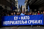 Vojislav Seselj, center, the leader of the ultranationalist Serbian Radical Party, and his supporters, march along a street during a protest in Belgrade, Serbia, Sunday, March 24, 2019. Members of the ultranationalist Serbian Radical Party gathered for a protest on Sunday in the Serbian capital to mark the 20th anniversary of the NATO led bombing campaign against Serbia in 1999. The banner reads 'EU + NATO, Enemies of Serbia!' in Serbian Cyrillic letters. (AP Photo/Marko Drobnjakovic)