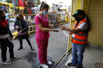 A shopper is given antibacterial gel as she enters Mercado Sonora, which reopened ten days ago with measures to reduce congestion and limit the spread of the coronavirus, in Mexico City, Thursday, June 25, 2020. (AP Photo/Rebecca Blackwell)