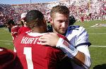 West Virginia quarterback Austin Kendall (12) and Oklahoma quarterback Jalen Hurts (1) embrace following an NCAA college football game in Norman, Okla., Saturday, Oct. 19, 2019. Oklahoma won 52-14. (AP Photo/Alonzo Adams)