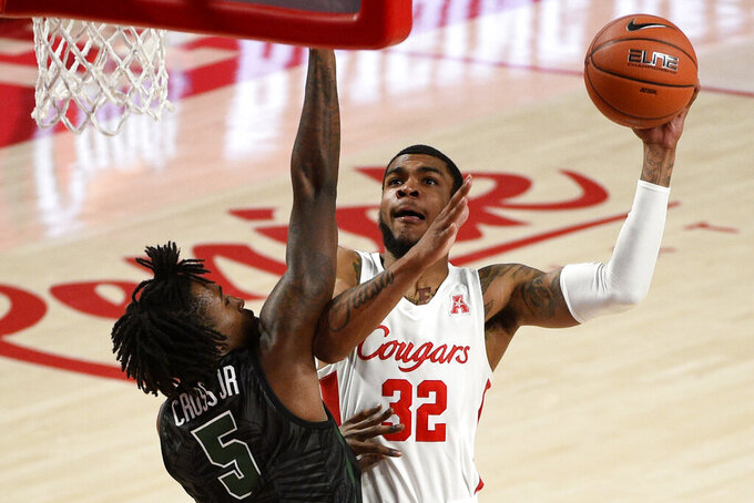 Houston forward Reggie Chaney (32) shoots as Tulane forward Kevin Cross defends during the second half of an NCAA college basketball game, Saturday, Jan. 9, 2021, in Houston. (AP Photo/Eric Christian Smith)