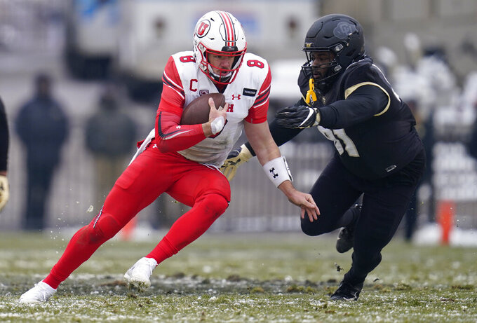 Utah quarterback Jake Bentley, left, is stopped after a short gain by Colorado defensive tackle Na'im Rodman the second half of an NCAA college football game Saturday, Dec. 12, 2020, in Boulder, Colo. Utah won 38-21. (AP Photo/David Zalubowski)