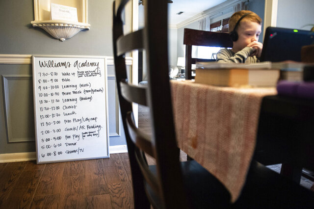 A board displays the Williams family's schedule as the children work on projects at home Friday, March 20, 2020 in Decatur, Ala. Emily Williams, their mother, is a third grade teacher at Austinville Elementary. (Dan Busey/The Decatur Daily via AP)