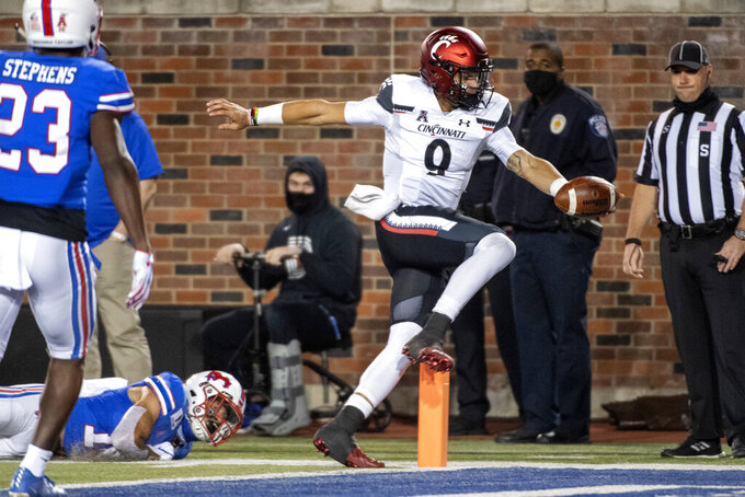 Cincinnati quarterback Desmond Ridder (9) runs for a touchdown past SMU safety Roderick Roberson Jr., bottom left, and defensive back Brandon Stephens (23) during the first half of an NCAA college football game Saturday, Oct. 24, 2020, in Dallas. (AP Photo/Jeffrey McWhorter)