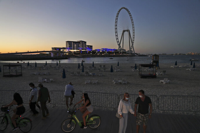Tourists and residents enjoy the sunset at the Jumeirah Beach Residence, in Dubai, United Arab Emirates, Tuesday, Jan. 12, 2021. Coronavirus infections are surging to unprecedented heights in the United Arab Emirates. But Dubai, the glimmering city-state powered by legions of foreign laborers and travelers, is resisting a lockdown during its peak tourism season. (AP Photo/Kamran Jebreili)