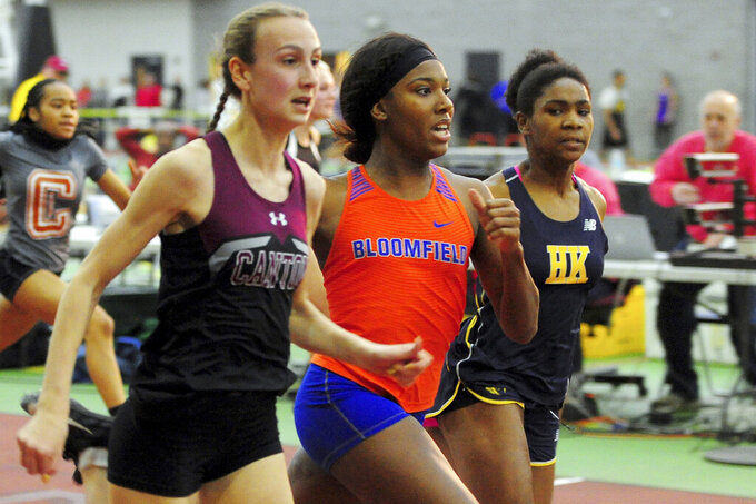In this Friday, Feb. 14, 2020 photo, Canton High School's Chelsea Mitchell, left, runs to beat Terry Miller, center, of Bloomfield, in the CIAC Class S track and field championships at Floyd Little Athletic Center in New Haven, Conn. center. Between 2017 and 2019, transgender sprinters Miller and Andraya Yearwood combined to win 15 championship races, prompting a lawsuit on behalf of four cisgender girls. (Christian Abraham/Hearst Connecticut Media via AP)
