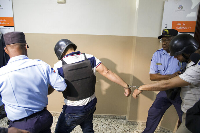 Police officers escort suspects implicated in the shooting of former Boston Red Sox slugger David Ortiz, Víctor Hugo Gómez Vázquez, left, and Alberto Rodríguez Mota, right, out of the courtroom in Santo Domingo Este, Dominican Republic, Saturday, June 29, 2019. Ortiz was shot in the back at a bar in the Dominican Republic on Sunday, June 9. (AP Photo/Tatiana Fernandez)