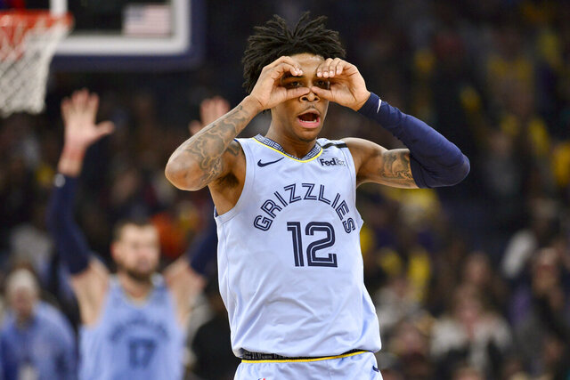 FILE - In this Feb. 29, 2020, file photo, Memphis Grizzlies guard Ja Morant (12) reacts after an assist to center Jonas Valanciunas (17) in the second half of an NBA basketball game against the Los Angeles Lakers in Memphis, Tenn. The young Grizzlies want to finish what they started, and that's accelerating the rebuilding process by earning the franchise's first playoff berth since 2017.  (AP Photo/Brandon Dill, File)
