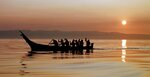 FILE - In this Aug. 20, 1998, file photo, Makah Indians paddle away from the rising sun as they head from Neah Bay, Wash., toward open Pacific Ocean waters during a practice for a planned whale hunt. Two decades after the Makah Indian tribe in the northwestern corner of Washington state conducted its last legal whale hunt from a hand-carved canoe, lawyers, government officials and animal rights activists will gather in a small hearing room in Seattle to determine whether the tribe will be allowed once again to harpoon gray whales as its people had done from time immemorial. (AP Photo/Elaine Thompson, File)