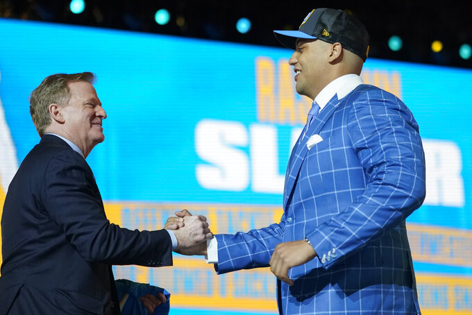 Northwestern tackle Rashawn Slater, right, greets NFL Commissioner Roger Goodell after he was chosen with the 13th pick by the Los Angeles Chargers in the NFL football draft Thursday April 29, 2021, in Cleveland. (AP Photo/Tony Dejak)