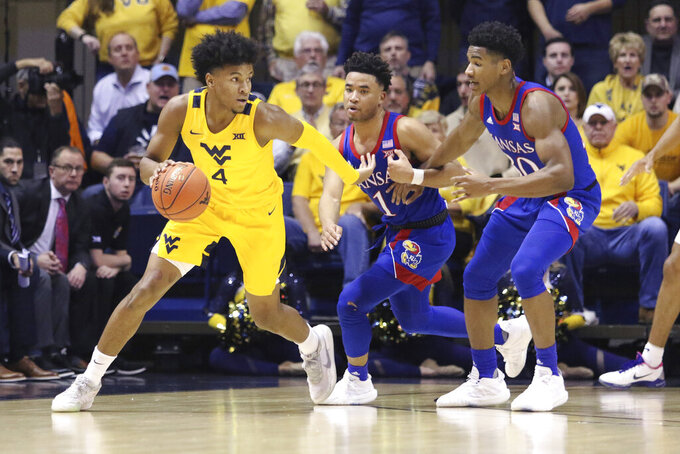 West Virginia guard Miles McBride (4) is defended by Kansas guards Devon Dotson (1) and Ochai Agbaji (30) during the first half of an NCAA college basketball game Wednesday, Feb. 12, 2020, in Morgantown, W.Va. (AP Photo/Kathleen Batten)