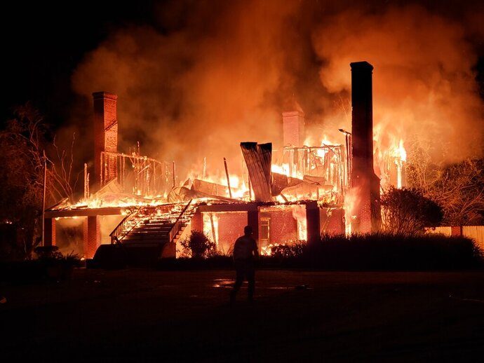 The Frogmore Plantation is fully engulfed in flames in Frogmore, La., Friday, July 26, 2019. The Frogmore Plantation, an 800 acre (730 hectare) property in Concordia Parish, includes a cotton gin that's on the National Register of Historic Places. (Sabrina Robertson/The Natchez Democrat via AP)
