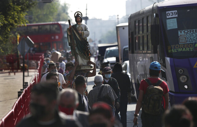 Faithful wearing protective face masks amid the new coronavirus, arrive to the San Hipolito Catholic church as part of the annual pilgrimage honoring Saint Jude, the patron saint of lost causes, in Mexico City, Wednesday, Oct. 28, 2020. Thousands of Mexicans did not miss this year to mark St. Jude's feast day, but the pandemic caused Masses to be canceled and the rivers of people of other years were replaced by orderly lines of masked worshipers waiting their turn for a blessing. (AP Photo/Marco Ugarte)